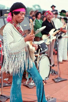 A MOST POPULAR RE-PIN: Jimi Hendrix in Woodstock Music Festival years, checking his guitar tuning, wearing long fringes on 1960s hippy frock. Great color photograph with drumkit & crowd members in background. See https://www.pinterest.com/pin/349732727288963400/ for Nice B&W portrait version of rock music festival day's blue jeans & tunic. RESEARCH #DdO:) - https://www.pinterest.com/claxtonw/jazz-and-all-that/ - JAZZ & ALL THAT at dairy farm in Catskills Mountains of NY. Pinned via Eduardo…