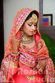 Punjabi bride with coral dupatta , gold maang tikka , nosering , gota work , coral lipstick , gold choker