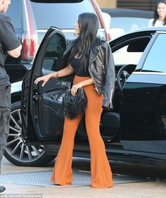 That'll wow them: Kourtney paired her remarkable flame-hued trousers with a black leather jacket and black fringe handbag