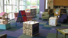 The early literacy area of the Addison Public Library's Children's Library (IL) has a doll house, pattern cubes, letter/number cubes, a flannel board, and other educational toys and materials to build early literacy skills in children.