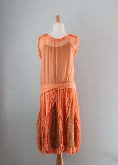1920s Dress The dress features a wide self-fabric attached sash at the dropwaist that is topped with a silk flower adorned with gold ribbon and little rosettes. The skirt is set with metallic gold lace insets trimmed in tiny ruffles. These ruffles also trim the neckline and sleeves. Back