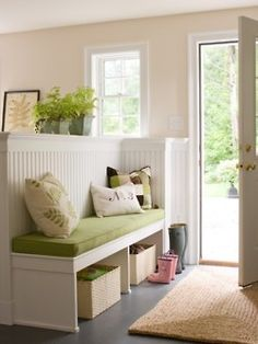 No entry hall? I have a solution! Put in a room divider that doubles as a bench and storage. Beautifully shown here.