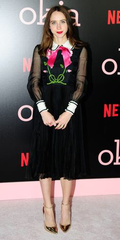 Zoe Kazan also showed us her version of Wednesday Addams in a dress with sheer sleeves, pleated skirt, floral embroidery, and a whimsical hot pink ribbon. A pair of gold pumps completed the look.
