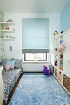 Ten wąski, ale długi pokój dziecięcy zagospodarowano niskim regałem, bo taki do samego sufitu za bardzo przytłoczyłby wnętrze. Mebel poza półkami ma praktyczne szuflady i szafki, w których można ukryć ubrania i mniej reprezentatywne rzeczy. Błękitny kolor łączy ścianę, roletę w oknie i dywan w spójną całość.
