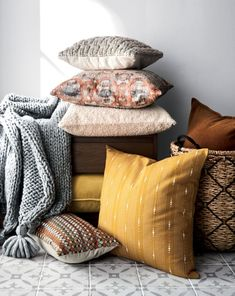 Strands of pure silk tussar are acid-dyed and then block printed by hand with metallic highlights for subtle glimmer. The luxurious fabric is then embroidered on hand-guided machines in a complex geometric design. Designed by Manish and Madhulika Tibrewal, the silk pillow is patterned in shades of orange, grey and neutrals and reverses to solid natural cotton. Skilled textile artists take a full day to complete each lumbar pillow. Due to its handcrafted nature, each one will be unique. Our…
