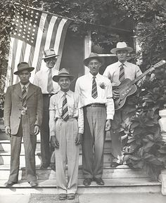 Five Mexican American men in white shirts and ties and fedoras pose on forties California Central Valley porch steps with American flag and guitar. 1940s vernacular photo snapshot
