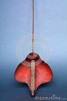 Vertical back view of handle punctured by moths and red hilt of a nineteen-twenties vintage training foil with a grey background