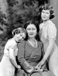 Queen Elizabeth of England, consort of King George VI, with the couple's two daughters, Princess Margaret (left) and Princess Elizabeth, heir presumptive.  Princess Margaret's pose here is simply precious.