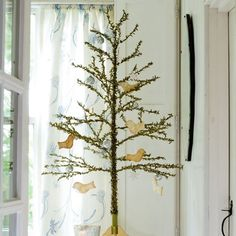 Country Christmas decorating ---  This is reminiscent of the small Victorian feather trees that also had few branches spaced well apart to show off the ornaments. Feather trees have a special class of tiny  ornaments scaled to the trees' small size.
