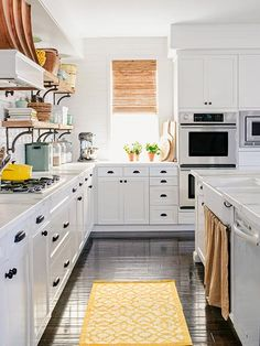 White paint and marble flatter the engineered walnut flooring in this kitchen. Homeowner Amber Haldane fashioned the sink skirt out of a @potterybarn curtain.