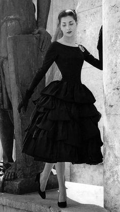 1955 Renée Breton is wearing 'Tambourin' a short evening dress of black silk faille from his AutumnWinter Collection of 1955-56