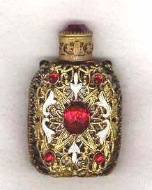 """Czech Perfume Bottle Filigree and Enamel Stones Jewels Red.   Gold colored filigree wraps around the whole bottle. On the front there is some white enamel and three small red """"stones"""" surrounding one large red """"stone"""". On each shoulder there is also a red stone. The screw-on cap with an intact dauber has a matching red """"stone"""" on top and is marked with a Czech tag on the side."""