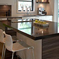 Armoires, tiroirs et huches de cette accueillante cuisine sont en thermoplastique d'un blanc immaculé. Les diverses surfaces de travail affichent par contre des matériaux, des couleurs et des épaisseurs variés.