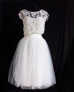 Robe de mariée courte, dentelle et jupe en tulle Pour une robe de mariée courte absolument romantique prenez un top réalisé dans une précieuse dentelle de calais doublé de soie dans une forme bustier, du biais pour border l'encolure bateau et le décolleté rond dans le dos. Ajoutez une robe mi-longue en tulle, composée d'une doublure coton pour le confort, deux épaisseurs de tulle rigide pour la tenue et de deux épaisseurs de tulle souple pour la finesse et la légèreté. Pour la touche finale…