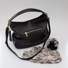 This functional everyday Hobo bag has a large compartment with detachable shoulder strap. Can be worn as a handbag or shoulder bag .