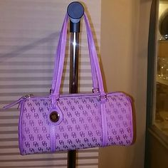 """Dooney & Bourke Shoulderbag The signature barrel shoulderbag is pink, has siver tone hardware, 2 of the 5 inside pockets zip.  There is a small stain on the lining.  The straps are leather.  The overall condition of the handbag is very good.  Approximately 5""""H × 11"""" L × 4.5"""" D, strap drop 9.5"""" Dooney & Bourke Bags Shoulder Bags"""