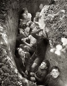 The Blitz. Kids hiding in a ditch while German bombers fly overhead.