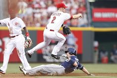 Zack Cozart #2 of the Cincinnati Reds turns a double play over Chris Denorfia #13 of the San Diego Padres during the game against at Great American Ball Park on August 10, 2013 in Cincinnati, Ohio. (Photo by Joe Robbins/Getty Images)