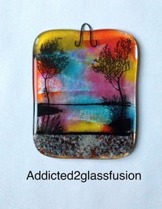 Cremains, Sunset Wall Hanging.  Your pet ashes or loved one's ashes are permanently encased between layers of glass in the fused glass wall hanging.  The ashes form the walkway through the rocks at the bottom.