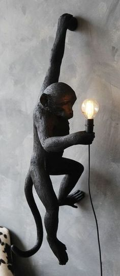 lifestyle image of Left-Hand Hanging Monkey Wall Lamp - Black - Suitable For Outdoors lit up on grey wall with black and white cowhide armchair in background Source by Lamps black