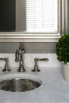 Elegant bathrom with gray grasscloth, silver leaf mirror, chrome faucet, marble counter and hammered metal undermount sink.