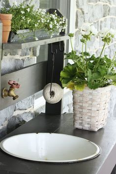 "StoneGable's potting bench: ""A chicken feeder overflowing with frilly white plants and a few little terracotta pots fill the narrow top shelf of the potting bench"".    NB String and hose bib..."