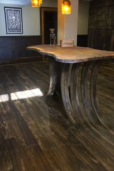 Flooring curves up from the existing wood to form the support for this live-edge walnut bar top.
