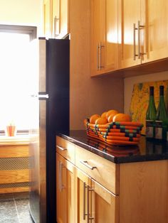 In this kitchen, light wood cabinets feature sleek, contemporary hardware. A basket of oranges adds a pop of color against the black countertops.