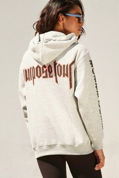 """This heathered knit sweatshirt features a drawstring hood, long sleeves, ribbed trim, a """"World Tour"""" graphic printed on the sleeves, and the graphic """"Purpose Tour"""" printed on the back."""