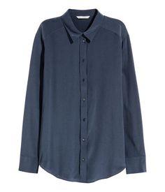 Mörkblå. PREMIUM QUALITY. En blus i crêppad mullbärssiden. Blusen har krage och knäppning fram. Rundad i nederkant.