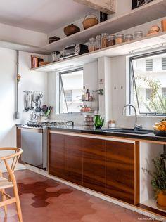 Cozinha integrada tem prateleiras de concreto e bancada de granito.