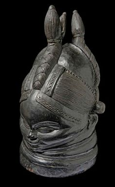 Sowei mask, Sierra Leone. This carved wooden mask (sowei) is designed to be worn over the head and danced whilst wearing a raffia costume.