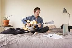 Guitarist Practicing Music on Bed with a Laptop - Cavan Images/Iconica/Getty Images