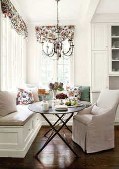 corner banquette seating with white wood bench, white cushion, white couch, black round metal table of A Comfortable Spot in the Corner