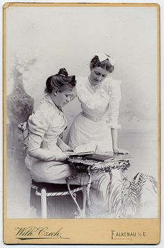 Victorian women looking over a book......