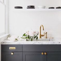 Black + white + unlacquered brass = simply chic. Henry in a kitchen by @grantkgibson. #WaterworksKitchen #HomeDesign