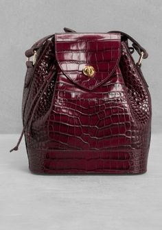 This endearing shoulder bag is made from glossy croco-embossed leather and features a drawstring and flap closure with gold-tone details. The adjustable long strap enables the bag to be carried cross-body.