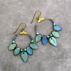 Brincos de KATE PURDY (EUA) - Blue Leaf Hoop Earrings -  Hoop earrings feature eye-catching iridescent blue leaf beads. A circle of blue Czech glass leaf beads and tiny iridescent seed beads are accented with sparkling turquoise Swarovski crystals. These handcrafted brass hoop earrings measure 1 inch round. Comfortable gold niobium ear wires are hypoallergenic. - 34 USD