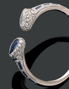 Van Cleef & Arpels. Années 1920-1925 Rare et exceptionnel bracelet rigide ouvert. Il se termine par deux motifs en fleur de lotus rehaussés par un diamant poire et un saphir poire en sertissure. L'ensemble est finement repercé et serti de diamants brillantés et de saphirs calibrés en ligne.