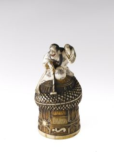 Netsuke of carved ivory depicting the dragon witch Kiyohime on the temple bell: Japan, 19th century.