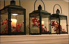 Three lanterns w/glowing candles and red berries. Good for the top of something (hutch, kitchen cabinets, shelf in the guestroom, etc.).