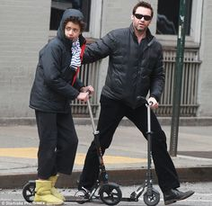 Protective dad: The Wolverine star put a loving hand on his son's back... Check out Hugh's awesome electric Micro scooter https://www.microscooters.com.au/scooters/adult-scooters/em0004-emicro-one