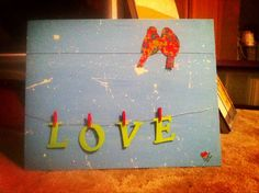 Made this for my boyfriend's momma. It's canvas, acrylic paint, wire, mini clothes pins and handmade paper.