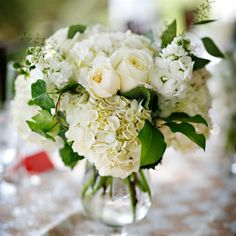White centerpieces full of roses, hydrangeas, ivy and stock were set on every table.
