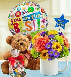 Mugable™ to Say You're The Best! •Signature Mugable ™ arrangement of orange carnations, assorted poms, purple monte casino and variegated pittosporum, with candy and plush bear #Flowers $29.99- $49.99