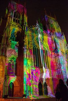 """Evoke by Usman Haque    A massive animated 80,000 lumen projection, that lights up the facade of York Minster. The facade is brought to life by members of the public, who use their own voices to """"evoke"""" colourful light patterns that emerge at the building's foundations and soar up towards the sky, giving the surface a magical feeling as it melts with colour."""
