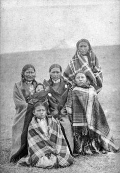Spotted Tail's wife and family, Native American (Sioux) woman, boys, girls, and baby pose outdoors, possibly at Pine Ridge Agency, South Dakota. Each person is wrapped in a blanket. The boys wear hair pipe chokers. Date [between 1875 and 1885]