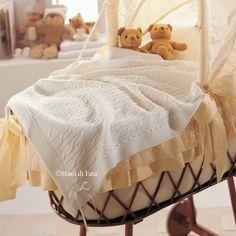 Copertina culla in pura lana con motivo trecce rifinita con passanastro in raso.