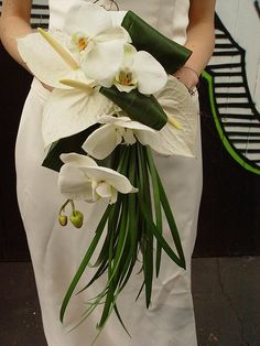 Elegant white bridal bouquet with phalaenopsis, anthurium, grasses and folded aspidistra leaves.