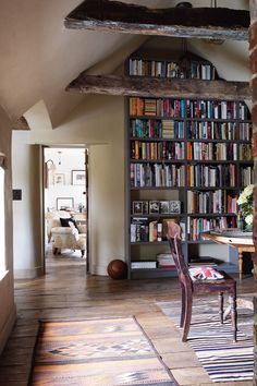 "Reclaimed ceiling beams were hollowed out to conceal steel structures in [link url=""http://www.houseandgarden.co.uk/interiors/real-homes/robin-muir-south-downs""]Robin Muir's study[/link], where the look of shelved books is reflected in a striped rug. [i]Taken from the October 2014 issue of House & Garden.[/i] Like this? Then you'll love [link url=""http://www.houseandgarden.co.uk/interiors/living-room""]From colour to decor, hundreds of living room pictures to inspire[/link]"